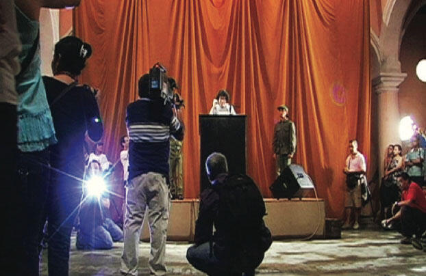 Tatlin's Whisper #6 (Havana Version), 2009. Stage, podium, microphone, loudspeakers, curtain, 2 people in military fatigues, dove, audience, and 200 disposable cameras, Wilfredo Lam Center, Havana. Courtesy of Berezdivin Collection, San Juan, Puerto Rico. El susurro de Tatlin #6 (version para La Habana), 2009. Plataforma, podio, micrófonos, baffles, telón, dos personas con vestimenta militar de faena, paloma, público y 200 cámaras desechables. Centro Wifredo Lam, La Habana. Cortesía Colección Berezdivin, San Juan, Puerto Rico.